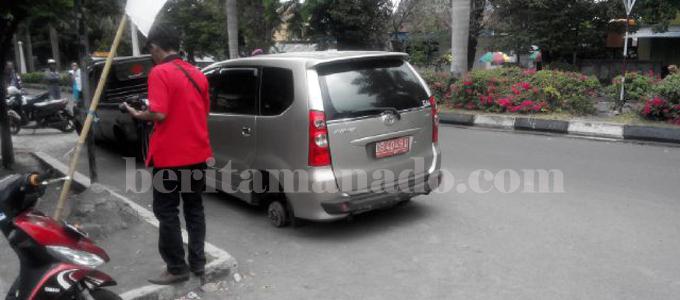 Mobil dinas Humas DPRD Bolmong yang rodanya dicabut (foto beritamanado)
