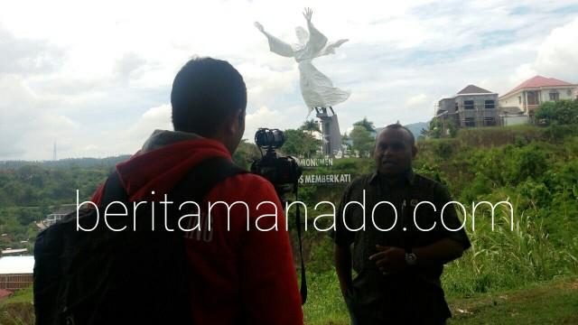 Pdt Paul sedang berfoto dengan latar Patung Yesus Memberkati