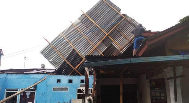 Warga gotong royong memperbaiki rumah yang rusak.