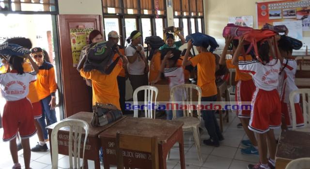 Para siswa satu per satu meninggalkan ruangan kelas, menuju lokasi aman.