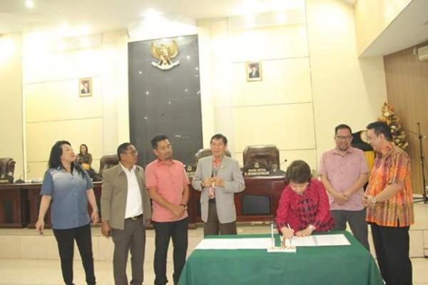 Ketua DPRD menandatangani berita acara.