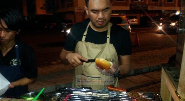 Pemilik Odanam Burger sedang menyiapkan pesanan burger