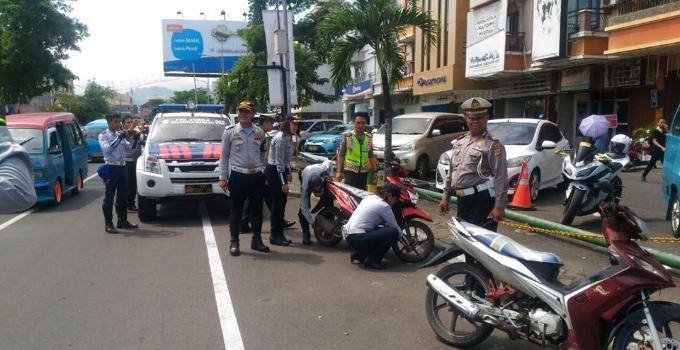 Petugas mengempiskan ban kendaraan yang parkir sembarangan