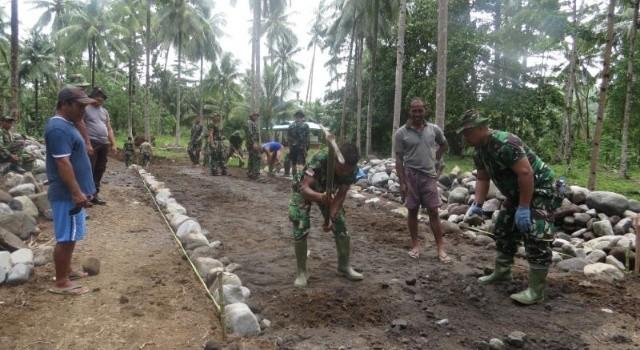 Satgas TMMD bersama masyarakat sedang melaksanakan pengerjaan jalan