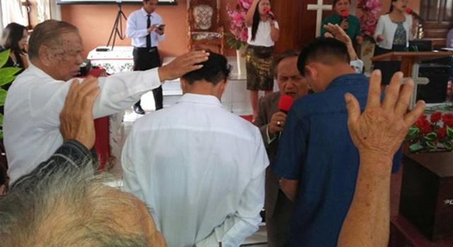 Dua anak muda yang di doakan di sebuah gereja di Desa Wolaang