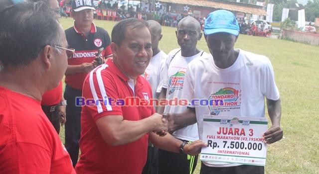 Bupati Minahasa Jantje Wowiling Sajow saat menyerahkan hadiah uang tunai kepada salah satu pemenang kategori 42 kilometer internasional
