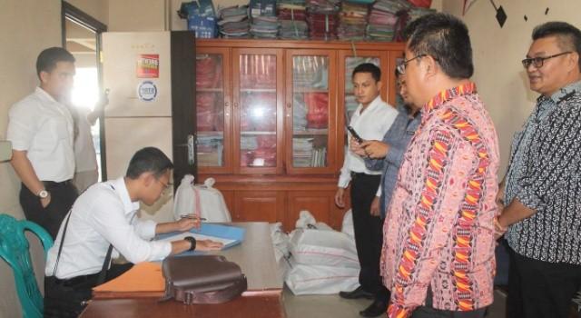 Kanit Tipikor Ipda Chandra Buana STK menandatangani berita acara penyerahan berkas bersama Kepala Inspektorat Minut Umbase Mayuntu.