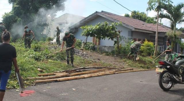 Para Prajurit Koramil 1310-06 Airmadidi saat sedang membersihkan bidang pekarangan kosong di Desa Kolongan Tetempangan.