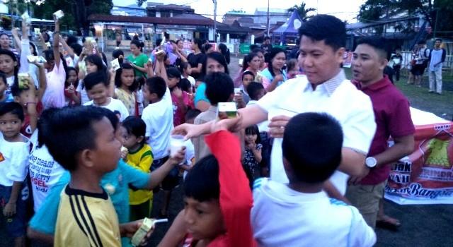 Melky Suawah saat membagikan susu kepada anak-anak