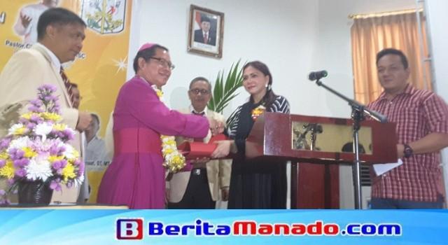 Bupati Vonnie Panambunan membuka kegiatan dan menyumbangkan uang tunai kepada panitia dan peserta yang diterima Uskup Manado Mgr Benedictus Untu.