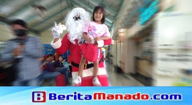 Santa Clauss bagi-bagi hadiah kepada anak-anak di Bandara Sam Ratulangi Manado