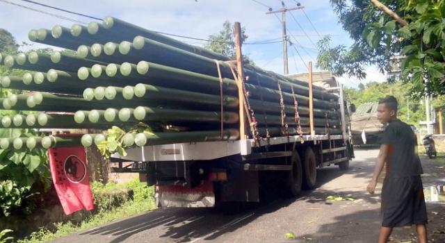 Truk besar bermuatan tiang lampu, yang melintasi jalan Likupang. Menariknya, truk ini berbendera PDIP.