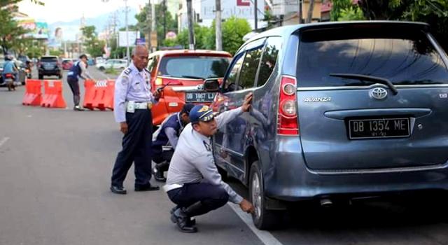 Petugas Dishub Manado sedang mengempeskan ban kendaraan yang parkir sembarangan