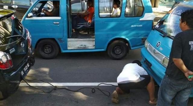 Foto yang sedang viral di Facebook, seorang driver taxol membantu menderek mikrolet yang mogok