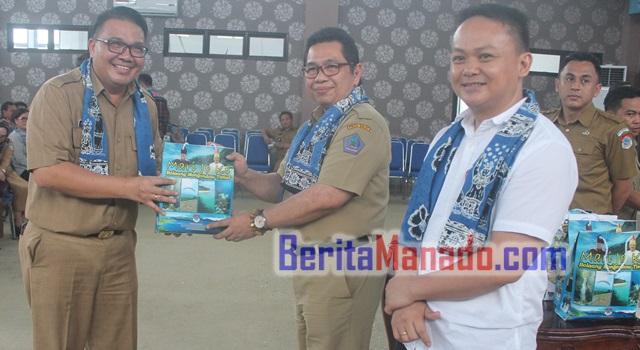 Agustivo Tumundo saat menerima souvenir dari Pemkab Bolaang Mongondow Timur yang diserahkan Kadisparda Sulut Daniel Mewengkang