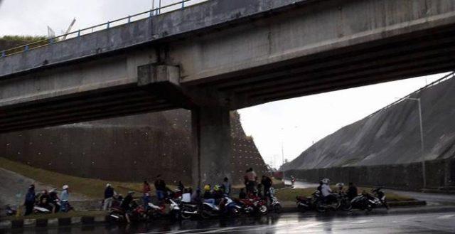 Bagian bawah interchange dijadikan tempat perteduhan pengendara sepeda motor ketika hujan