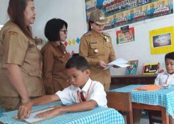 Bupati Minut Vonnie Panambunan membagikan lembar soal kepada peserta ujian.