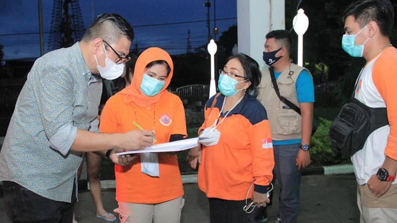 Toar Palilingan Jr (kiri) menyerahkan bantuan di Pos Bantuan Kita di pendopo Kantor Wali Kota Manado.